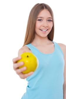あなたとリンゴを共有します。青リンゴを伸ばして、白で孤立して立っている間笑顔で陽気な10代の少女
