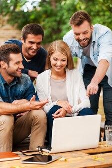 기발한 아이디어를 공유합니다. 야외에서 함께 일하는 동안 노트북을 보고 있는 쾌활한 젊은 사람들의 그룹