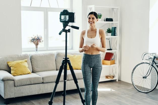 経験の共有。自宅で時間を過ごしながらソーシャルメディアビデオを作るスポーツウェアの美しい若い女性