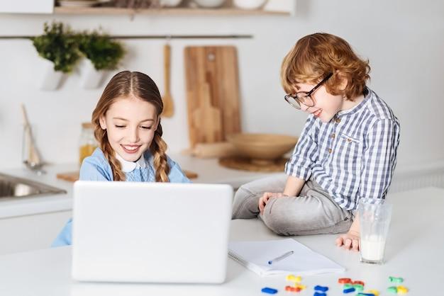 경험 공유. 테이블에 그녀의 옆에 앉아있는 동안 그녀의 컴퓨터를 사용하여 시험을 위해 공부하는 그의 형제를 관찰하는 매력적인 매력적인 잘 생긴 소년