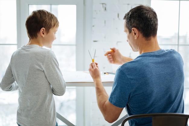 経験の共有。コンパスを持って、青写真の作成に取り組んでいる間、コンパスを操作する方法を息子に示す快適な若いエンジニア