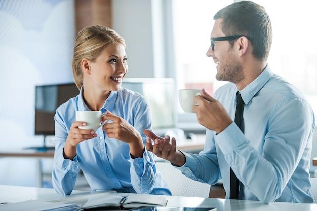 新鮮なニュースを共有する。コーヒーを片手に、一緒に仕事をしながら何かを話し合う正装の2人の楽しい若者