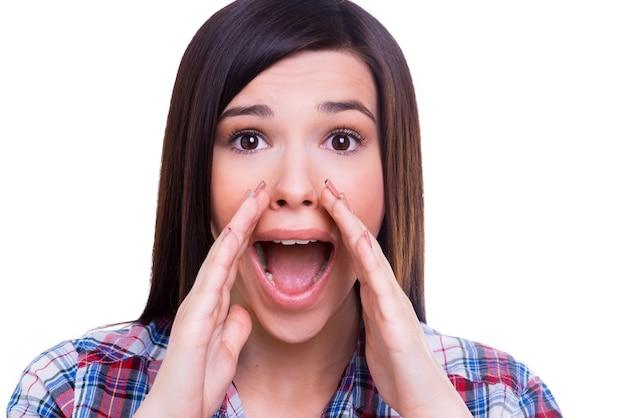 あなたと新鮮なニュースを共有します。白で隔離されている間口の周りに手をつないで叫んで驚いた若い女性