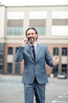 良いたよりを分かち合う。良いニュースを共有しながら妻を呼び出す陽気なハンサムな白髪のビジネスマン