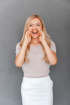 Делимся хорошими новостями. счастливая молодая женщина со светлыми волосами, взявшись за руки возле ее рта и