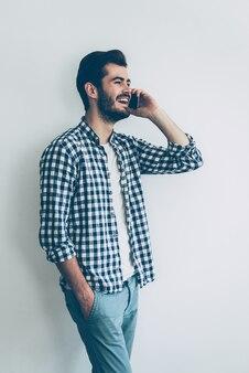 良いたよりを分かち合う。携帯電話で話し、笑顔で幸せな若い男