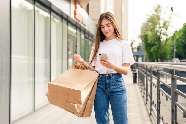 良いたよりを友達と共有する。屋外に立っている間買い物袋と携帯電話を保持している美しい若い笑顔の女性のクローズアップ