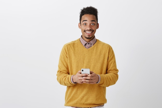 Sharing great news with friend. portrait of happy thrilled dark-skinned man in trendy outfit, holding smartphone, gazing with broad smile, being on cloud nine from happiness