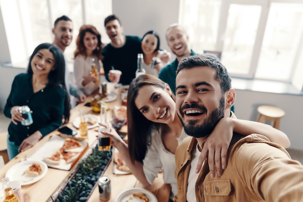 幸せな瞬間を共有します。屋内でディナーパーティーをしながら笑顔のカジュアルウェアの若者の自画像