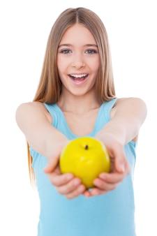 あなたと健康的な食べ物を共有します。青リンゴを伸ばして、白で孤立して立っている間笑顔で陽気な10代の少女