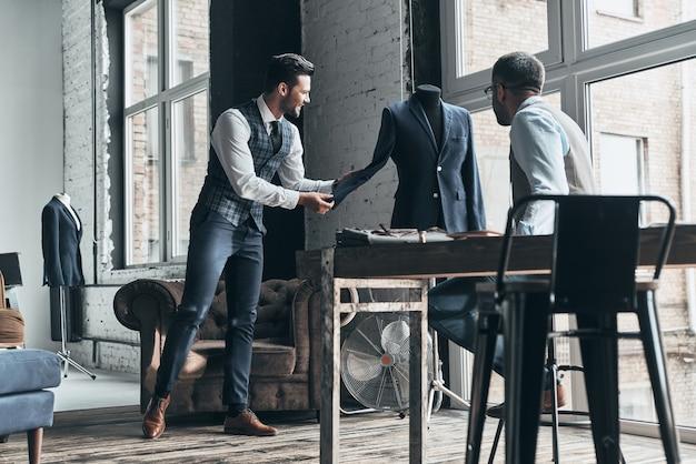 아이디어를 공유합니다. 워크샵에 서 있는 동안 토론하고 웃고 있는 두 젊은 유행 남자