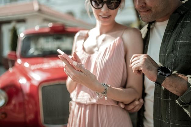 관심사를 공유합니다. 그녀의 스마트폰에 그녀의 관심 남편 사진을 보여주는 웃는 여자 거리에서 그와 함께 서. 프리미엄 사진