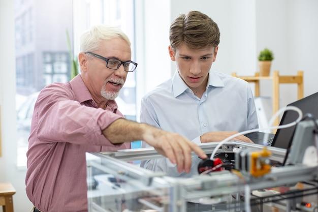 知識の共有。メカニズムの重要な部分を指差しながら、若いインターンに3dプリンターについて指導する経験豊富なシニアエンジニア