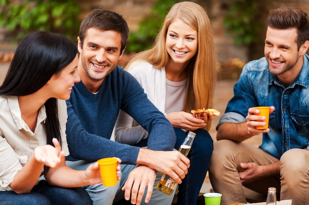 Sharing the latest news. group of happy young people talking to each other and drinking while sitting outdoors
