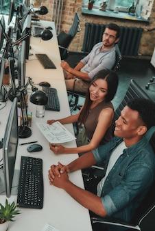 Обмен новыми идеями вид сверху многонациональной команды, работающей на компьютерах и общающейся с