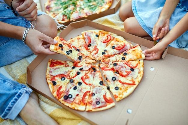 Делюсь пиццей, руки берут кусок пиццы из коробки на открытом воздухе,