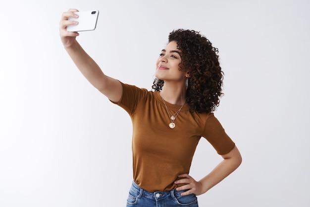 긍정적인 감정 인터넷 청중을 공유합니다. 매력적인 쾌활한 세련된 라이프 스타일 여성 블로거는 셀카를 찍는 스마트 폰을 들고 팔을 뻗어 행복한 미소 얼굴 표정 전화 카메라를 만듭니다