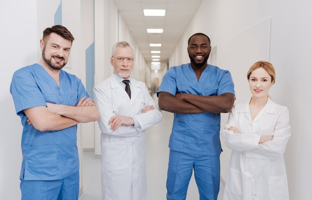 積極性を共有する。病院で働き、積極性を表現しながら腕を組んで立っている陽気な熟練した明るい開業医