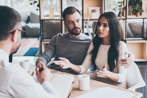 의사와 문제를 공유합니다. 책상에 함께 앉아 있는 동안 심리학자에게 문제를 말하는 젊은 부부