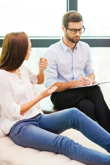 Sharing problems with professional. worried young woman sitting at the chair and gesturing while male psychiatrist sitting close to her and writing something in his clipboard