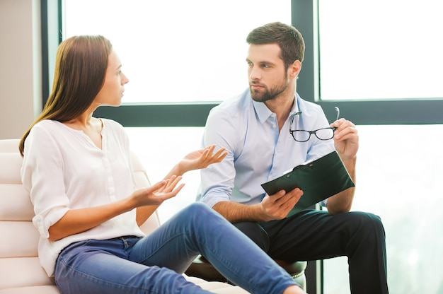 Sharing problems with psychiatrist. worried young woman sitting at the chair and gesturing while male psychiatrist sitting close to her and holding clipboard