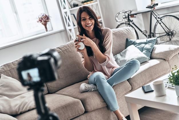 製品の利点を共有する。ソーシャルメディアビデオを作成しながら美容製品を保持し、笑顔の美しい若い女性
