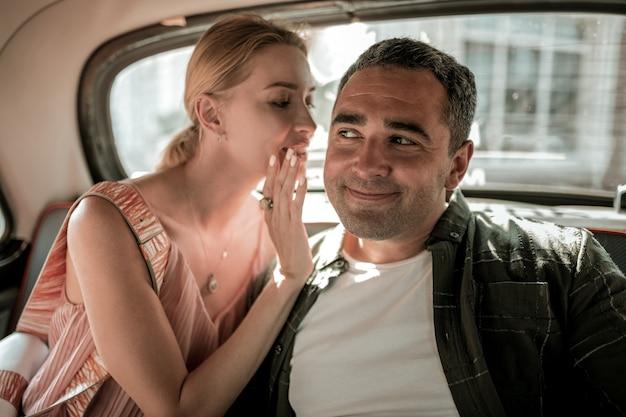 비밀을 공유합니다. 관심 있는 남편에게 자동차 운전사에 대한 생각을 속삭이는 웃는 여자.