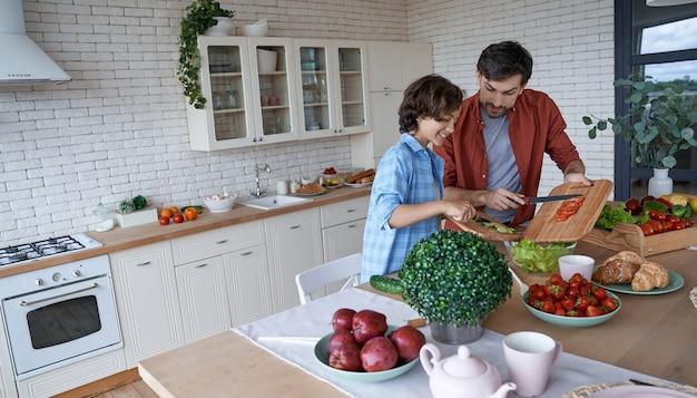 スキルを共有する若いお父さんと彼の小さな幸せな息子が一緒に野菜サラダを準備する