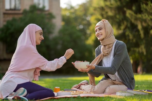 블루 베리 나누기. 야외에서 점심을 먹으면서 친구와 블루 베리를 공유하는 히잡을 착용 한 친구