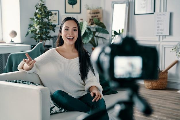 いくつかの新鮮なアイデアを共有します。彼女のブログの新しいビデオを作成しながら身振りで示すと笑顔の美しい若い女性