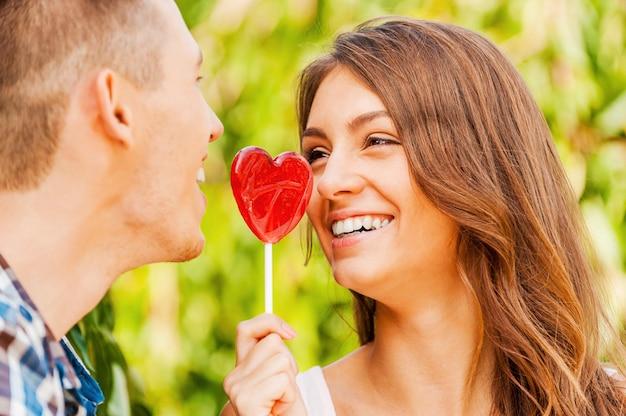 달콤한 사랑을 나눕니다. 롤리팝을 들고 남자친구가 그것을 맛보려고 하는 동안 웃고 있는 젊은 여성