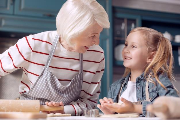 중요한 팁을 공유합니다. 그녀의 할머니가 쿠키를 만들고 그녀와 채팅하고 과정을 논의하는 동안 그녀의 경험을 공유하고 반죽을 굴리는 동안 사랑스러운 어린 소녀