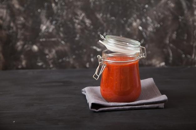 ガラスの瓶に入ったシャリッサのスパイシーなポッドパヴァは、リネンのナプキンの上に立っています。伝統的な郷土料理。スペアをコピーします。