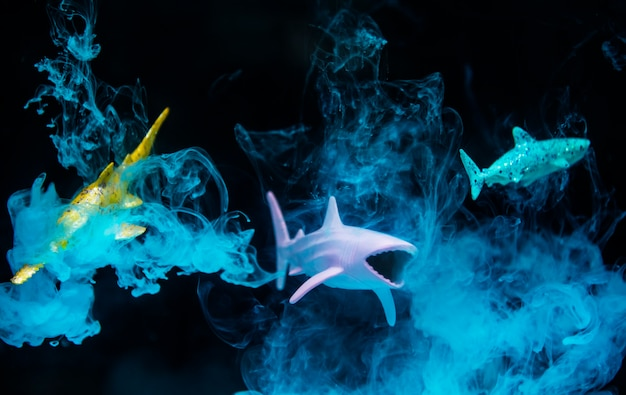 Shark figures in water with negative effect and blue smoke