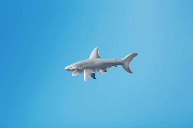 空き領域のある青い背景のサメのおもちゃ。