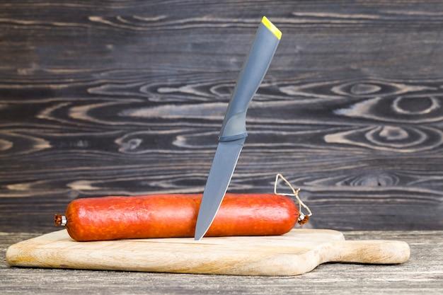 날카로운 검은 칼과 나무 도마에 소시지 전체 스틱, 집에서 음식