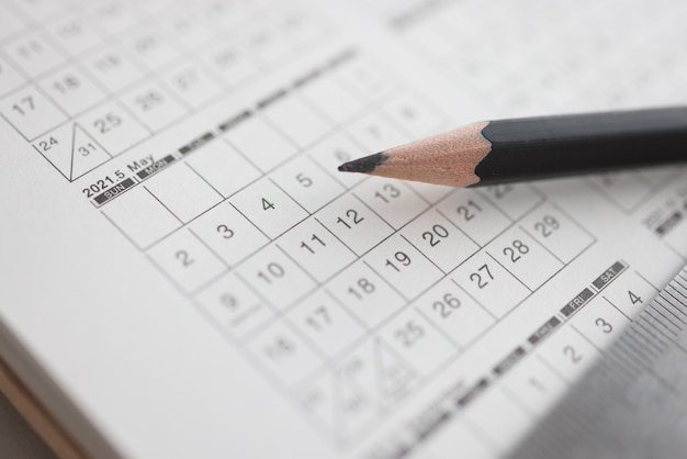 Sharp black pencil lying on calendar closeup
