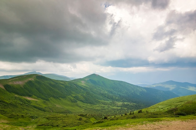 鋭い緑の山々のピークと劇的な雲の風景の空