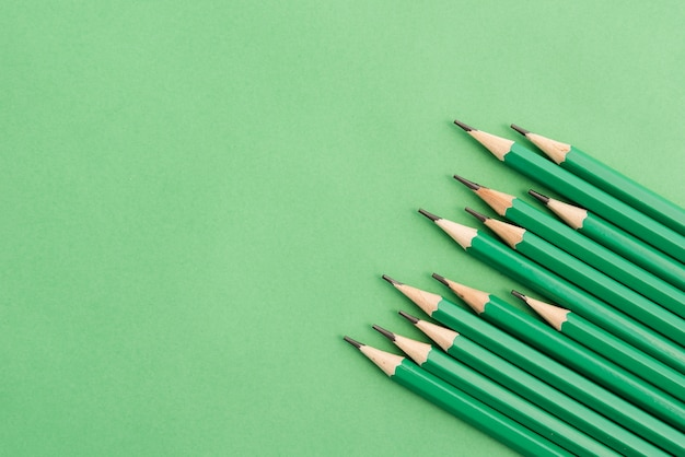 Sharp green pencil at the corner of plain background
