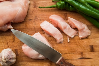 Sharp knife and raw chicken slices on cutting board with garlic and green chili