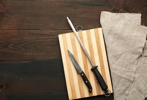Острый нож и точилка с ручкой на деревянном фоне