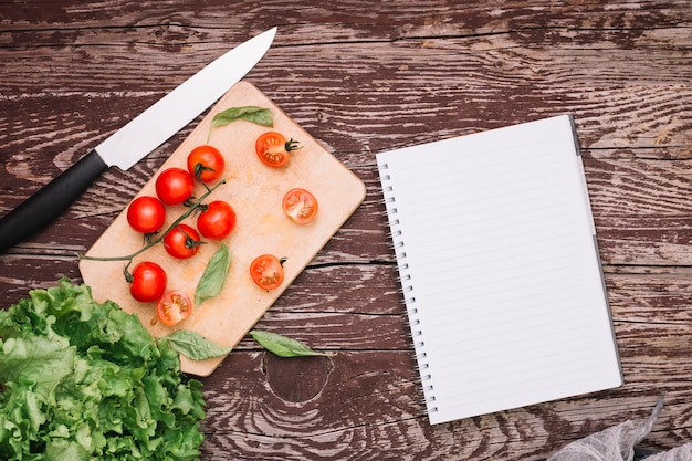 Sharp knife; basil; cherry tomatoes and lettuce with spiral notepad on wooden surface