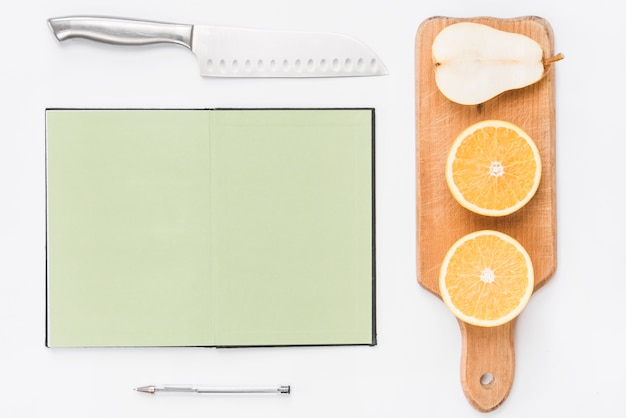 Sharp knife; blank page notebook; pen; halved oranges and pear on white background