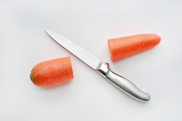 Sharp knife cut half carrot on white background.