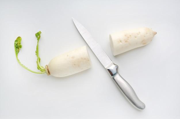 Sharp knife cut half radish on white background.