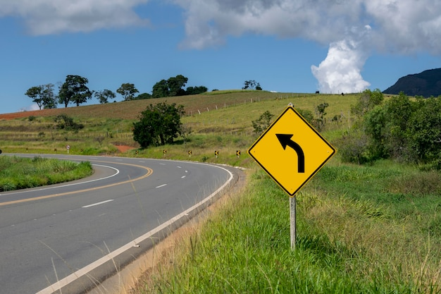 Sharp left turn signpost on the road
