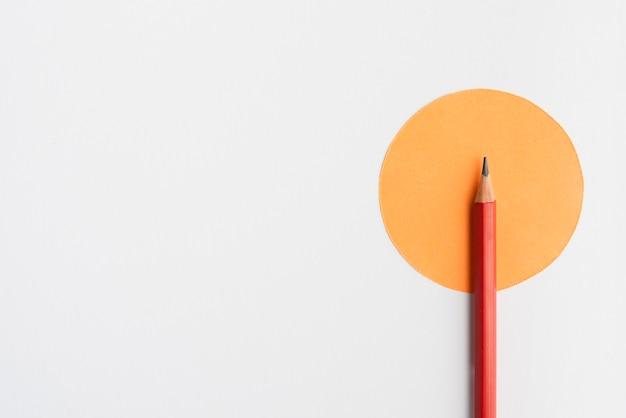 Острый карандаш на оранжевой бумаге круглой формы на белом фоне