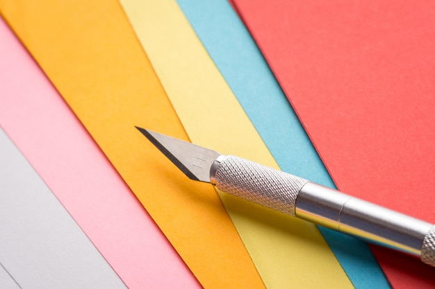 Sharp professional scalpel on the background of coloured papers