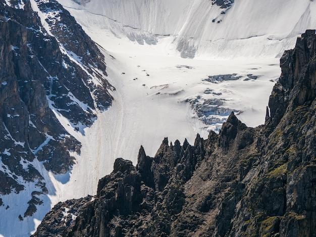 날카로운 바위. 특이한 모양의 뾰족한 돌이 있는 고원 풍경. 햇빛에 푸른 하늘 아래 눈 사이에 큰 금이 간 뾰족한 돌이 닫혀 있는 멋진 산 풍경