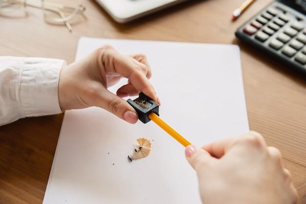 鉛筆を研ぐ。オフィスで働いている白人女性の手のクローズアップ。